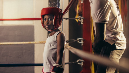 Kid wearing boxing gloves and headgear standing in a corner of a boxing ring. Small boy standing inside a boxing ring with his coach behind him. Stock fotó