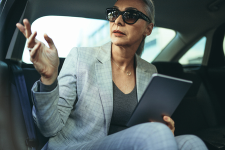 Beautiful mature businesswoman sitting on back seat of a car and looking outside the window. Female business executive travelling by a car.