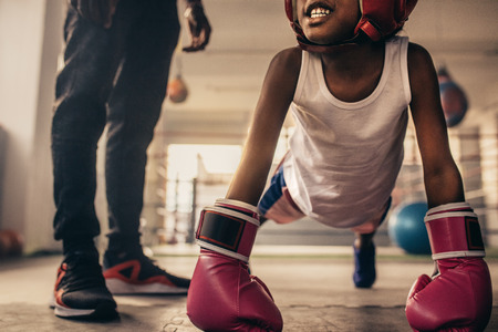 Boxing kid doing push ups wearing boxing gloves with his trainer standing beside him. Boxing kid doing warm up exercises inside a boxing gym.