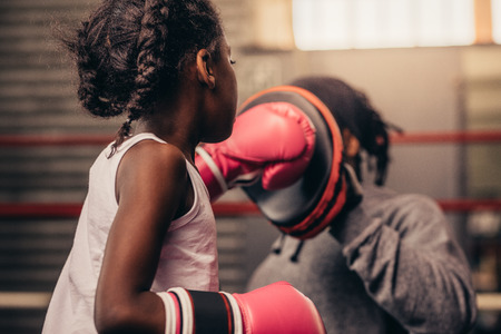 Girl wearing boxing gloves straining with her coach. Boxing kid practicing punches on a punching pad with her coach. Stock Photo