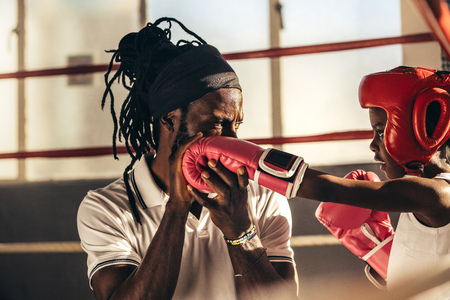 Kids wearing boxing gloves and headgear learning boxing from his coach. Trainer teaching techniques of boxing to a kid.