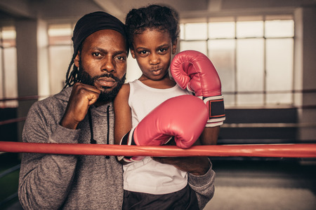 Kid wearing boxing gloves with her trainer standing in a boxing gym. Trainer with a kid boxer standing together showing their fist.