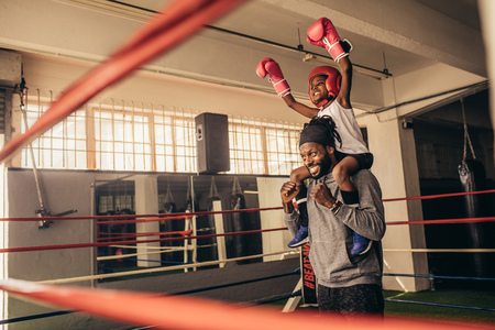 Trainer carrying a boxer kid on shoulders celebrating a win. Kid in boxing gear sitting on shoulder of coach with raised hands. Stock Photo