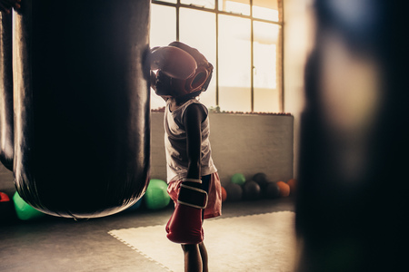Tired kid in boxing gloves and headgear leaning against a punching bag. Boxing kid standing tired after practice.