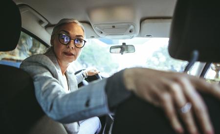 Portrait of senior woman in driving a car in reverse. Senior caucasian female driving a vintage car.