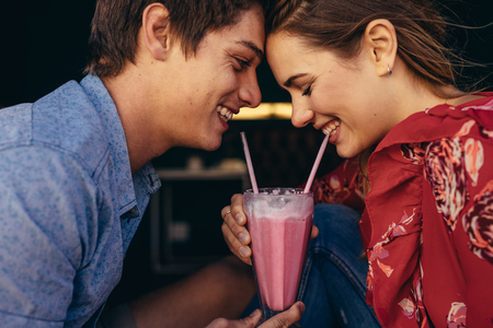 Close up of a happy couple sharing a milkshake with two straws. Smiling man and woman on a date sitting at a restaurant sharing a milkshake. Stock Photo - 111938667