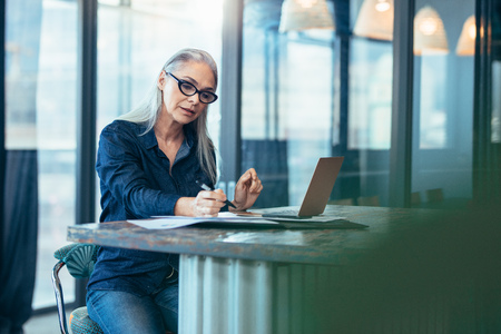 Portrait of senior woman sitting at table in office and reading few paper work. Business manager working on some documents at office. Stok Fotoğraf - 111938705