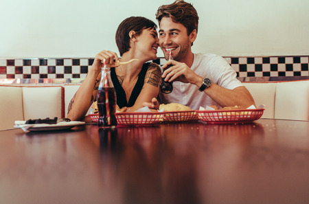 Smiling woman sitting close beside her partner at a restaurant and eating food. Romantic couple sitting in a diner with food and soft drinks on the table. Banco de Imagens
