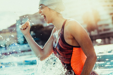 Excited female swimmer with clenched fist celebrating victory in the swimming pool. Woman swimmer cheering success in pool wearing swim goggles and cap. Stock Photo