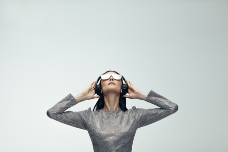 Young woman in silver outfit wearing headphones and looking up over grey background. Fashionable female model in futuristic look.