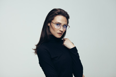 Portrait of confident woman in black dress wearing glasses. Female model in studio staring at camera with blank expression on grey background. Фото со стока