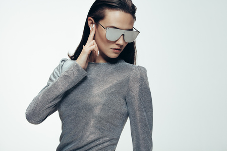 Portrait of young woman in trendy sliver outfit and mirrored glasses with fingers over her ear. Woman in futuristic style grey white background.