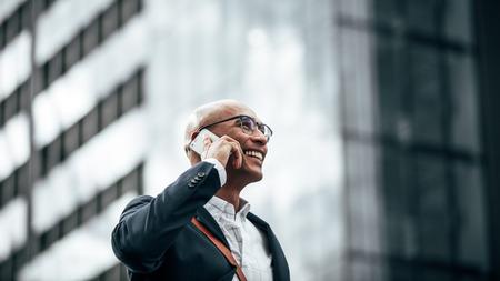 Man in formele kleding met een kantoortas die op straat loopt terwijl hij op een mobiele telefoon praat. Glimlachende zakenman die over de mobiele telefoon praat terwijl hij naar kantoor reist met een glazen gevelgebouw op de achtergrond.