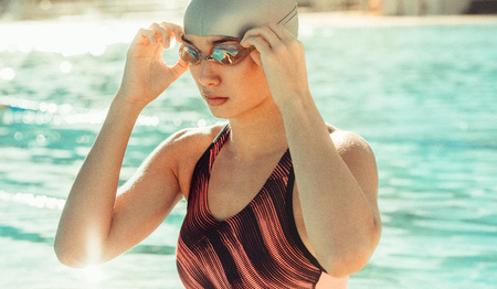 Portrait of sporty woman in swimsuit. Female swimmer by the pool after a swim. Stock Photo - 111939367