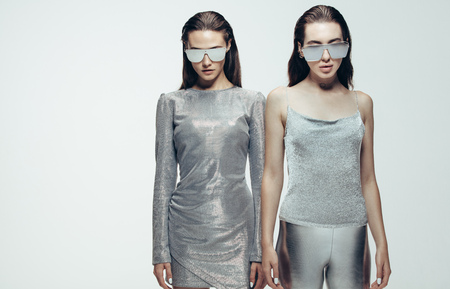 Portrait of two young women in silver outfit and mirrored sunglasses. Female models in futuristic look standing on grey background.