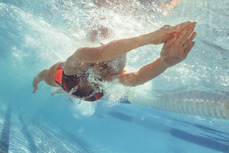 Underwater shot of female swimmer gliding in pool. Female swimmer stretched with the arms to the front with head between the arms and the feet to the back Imagens