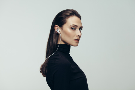 Portrait of beautiful woman in black top wearing earphones staring at camera. Studio shot of young beautiful woman as secret agent against grey background. Фото со стока