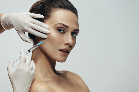 Young beautiful woman having skin injections against grey background. Female getting anti aging shots in her face by beautician.
