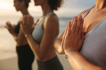Close up of women doing yoga standing at the beach with joined palms and closed eyes. Three women in fitness wear doing yoga and meditation standing at the seashore.