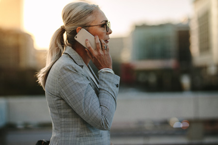 Side view of senior business professional walking outside on road talking on cell phone. Mature businesswoman walking outdoors on street with mobile phone.