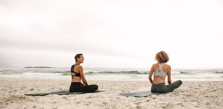 Rear view of two women in fitness wear practicing yoga sitting on the beach. Fitness women sitting on yoga mats doing yoga facing the sea.