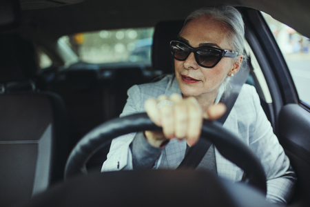 Stylish mature businesswoman driving her car and looking away. Senior woman wearing sunglasses at a wheel of a modern car about to take a turn.