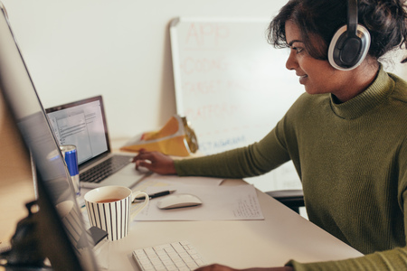 Female programmer working in office. Woman looking at laptop while coding on desktop computer.