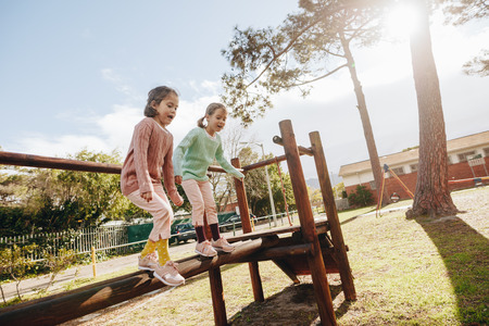 Cute little girls having fun on outdoor playground. Twin sisters jumping from wooden log at the park on sunny day. Stok Fotoğraf - 111939733
