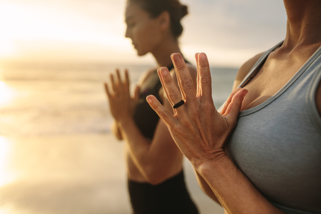 Close up of woman meditating at the beach with joined hands. Two yoga women standing at the beach with closed eyes and joined palms with sun flare in the background. Foto de archivo - 111939759