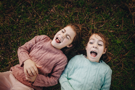 Top view of two little girls lying on green grass and laughing. Twins sisters enjoying outdoors at the park.