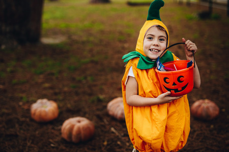 Portrait of cute little girl in Halloween costume holding pumpkin bucket outdoors at the park. Little girl child out for trick or treating on Halloween outdoors. Stock Photo