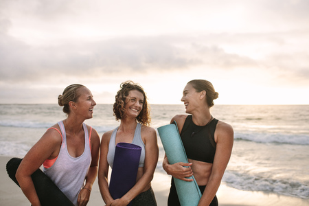 Smiling women at the beach talking to each other holding yoga mats. Fitness women standing at the sea shore to do yoga.