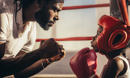 Boxing coach and kid training inside a boxing ring. Close up of a boxing kid in boxing gloves and headgear learning boxing from his coach. Stock Photo