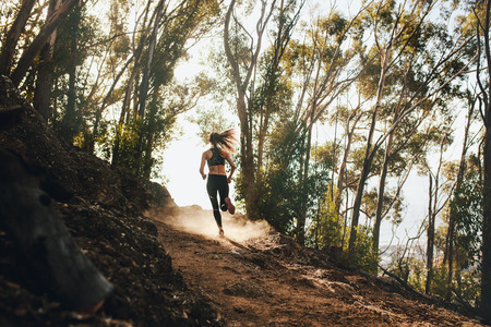 Rear view of woman trail running on a mountain path. Runner working out in beautiful nature.