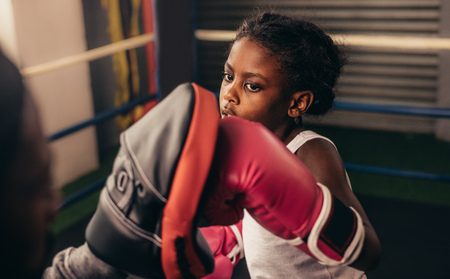Close up of a kid training inside a boxing ring. Kid boxer wearing boxing gloves practicing punches on a punching pad.