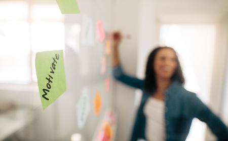 Vervaag het beeld van een zakenvrouw die plaknotities op de glazen wand plakt met de nadruk op een post-it-notitie die erop is geschreven.