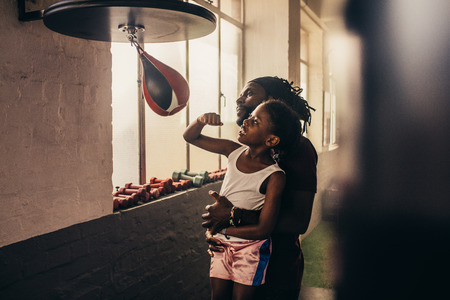 Kid punching on a speedball at a boxing gym with the help of his coach. Trainer lifting a kid for punching at a speedball.