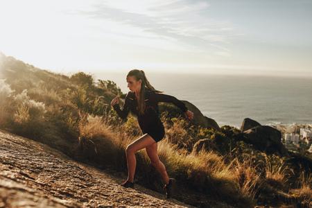 Monter une jeune femme en courant sur un sentier de montagne rocheuse. Femme trail runner s'entraînant pour la course en montée.