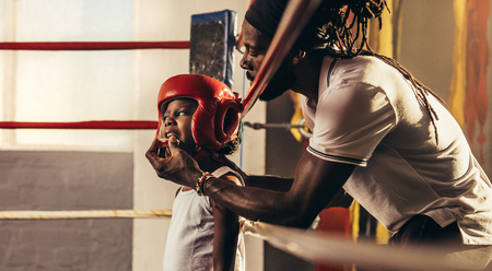 Coach fixing a teeth guard to a boxing kid before a fight. Kid getting ready for a fight standing inside a boxing ring wearing a head guard.