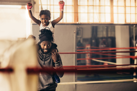 Boxer kid sitting on the shoulders of coach with raised arms celebrating victory.