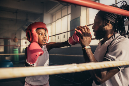 Kid wearing boxing gloves and headgear hitting punches on hands of his trainer. Boxing kid training with his coach inside a boxing ring.