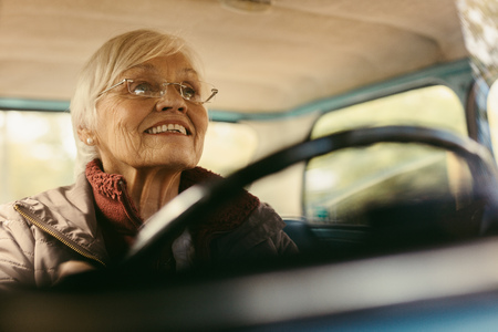 Senior woman driving car on winter day concentrating on the road. Elderly female wearing glasses driving a car carefully.