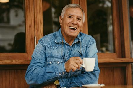 Ritratto dell'uomo anziano allegro che mangia caffè al caffè. Uomo anziano sorridente che si rilassa al caffè.