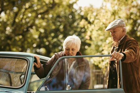 Old caucasian man being a gentleman and opening the car door for his date. Woman getting into the car with man opening the door on winter day. Stock Photo