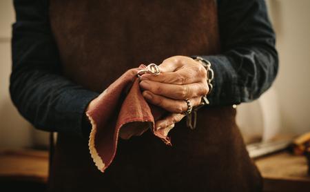 Hände der Juwelierin, die altmodischen Silberschmuck mit einem Tuch poliert. Schmuckmacherin wischt in ihrer Werkstatt einen Ring mit Stoff ab.