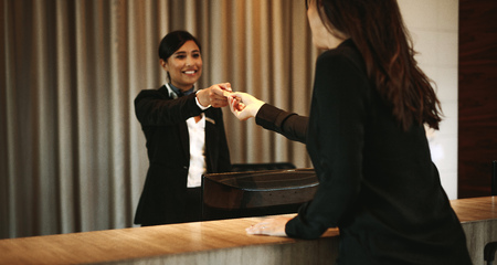 Female guest taking room key card at hotel check-in desk. Female receptionist giving room key to client in hotel. 版權商用圖片