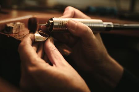 Hände der Juwelierin, die eine Ringoberfläche mit Schleifmaschine poliert. Goldschmied macht ein Schmuckstück an ihrer Werkbank. Standard-Bild