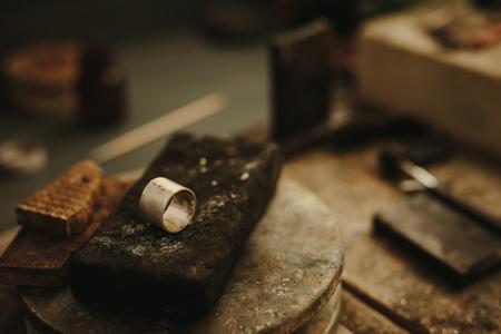 Ring op juwelierwerkbank met kleine stukjes metaal op de verbindingsrand klaar om te solderen. Ring maken in sieraden workshop. Juwelier werktafel.