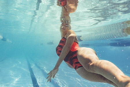 Underwater shot of female swimmer in action inside pool. Fit young female swimmer training in the pool.