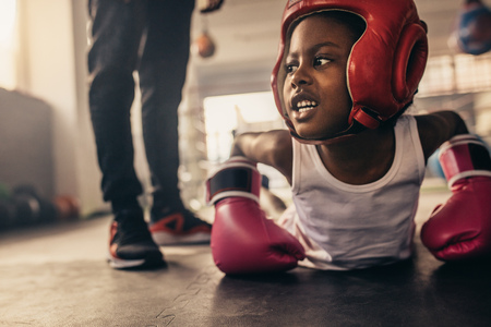 Kid wearing boxing gloves and headgear doing push ups. Kid doing warm up exercises before starting his boxing training. Stock fotó
